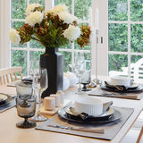 Wooden table in dining room with elegant table setting Stock Photo