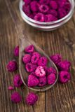 Wooden table with Dried Raspberries, selective focus. Raspberries dried as high detailed close-up shot on a vintage wooden table; selective focus Royalty Free Stock Image