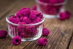 Wooden table with Dried Raspberries, selective focus. Raspberries dried as high detailed close-up shot on a vintage wooden table; selective focus Stock Photography