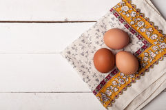 Wooden table, eggs and tablecloth Royalty Free Stock Photos
