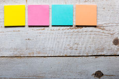 Wooden table with empty colorful sticky notes Royalty Free Stock Photography