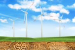 Wooden table with empty space on nature background with power turbines royalty free stock photos
