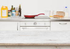 Wooden table in focus over blurred baking ingredients on kitchen Stock Photo