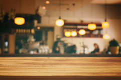 Wooden table in front of abstract blurred restaurant lights background. Image of wooden table in front of abstract blurred restaurant lights background Royalty Free Stock Image