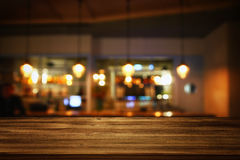 Wooden table in front of abstract blurred restaurant lights. Image of wooden table in front of abstract blurred restaurant lights background Stock Images