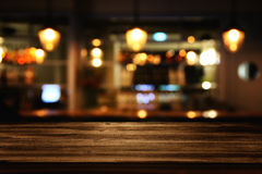 Wooden table in front of abstract blurred restaurant lights. Image of wooden table in front of abstract blurred restaurant lights background Stock Image
