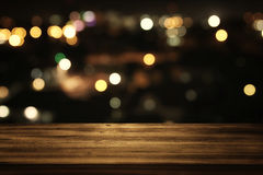 Wooden table in front of abstract blurred restaurant lights. Image of wooden table in front of abstract blurred restaurant lights background Royalty Free Stock Photos