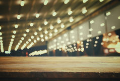 Wooden table in front of abstract blurred resturant lights
