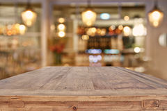 Wooden table in front of abstract restaurant lights background. Image of wooden table in front of abstract blurred restaurant lights background stock photography