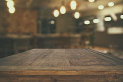 Wooden table in front of abstract restaurant lights background. Image of wooden table in front of abstract blurred restaurant lights background Royalty Free Stock Image
