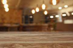Wooden table in front of abstract restaurant lights background Royalty Free Stock Photo