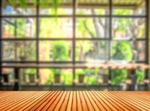Wooden table in front of blurred coffee shop background royalty free stock photography