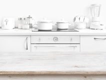 Wooden table in front of blurred white kitchen bench interior. Background Royalty Free Stock Photo