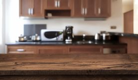 Wooden table in front of defocused modern kitchen counter top royalty free stock photography