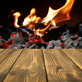 Wooden table in front of the fire and flames in the background Stock Photo