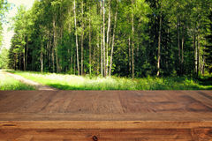 wooden table in front green forest trees landscape background. for product display and presentation Stock Photos