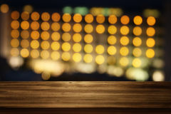 wooden table in front of night bokeh hotel. Ready for product display montages Stock Images