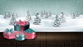 Wooden table with gift boxes in front of winter forest landscape stock photos