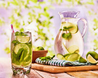 On wooden table is glass jug with transparent drink. Stock Photos