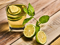 On wooden table is glass with mohito drink and lime. Royalty Free Stock Photo