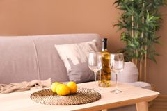 Wooden table with glasses, bottle of wine and lemons in living room stock photography