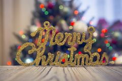 A gleaming Merry Christmas inscription on a wooden table against decorated Christmas tree. A wooden table with a gleaming gold Merry Christmas inscription Royalty Free Stock Image
