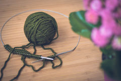 On a wooden table a green ball of wool, metal spokes and a pink. Flower in a pot. Knitting closeup Royalty Free Stock Image