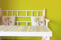 Wooden table with green wall. Wooden table and chair with pillow royalty free stock photos