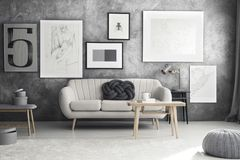 Grey sofa in living room. Wooden table at grey sofa with knot pillow against textured wall with posters in living room with pouf Royalty Free Stock Image