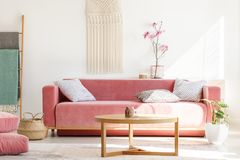 Free Wooden Table In Front Of Red Sofa In Pastel Living Room Interior Stock Images - 122122704