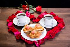 On the wooden table, inside the heart of the rose petals are two cups of coffee and a plate with biscuits. Outside is a rose flowe. R. Front view Stock Photos