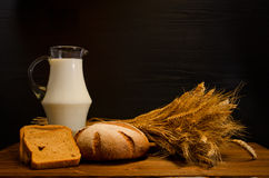 Wooden table with a jug of milk, rye bread and a sheaf, a black background Stock Image