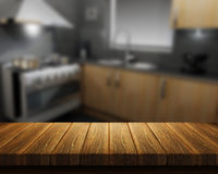 Wooden table with kitchen in background Stock Image