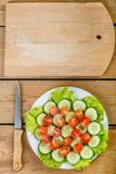 A wooden table is a knife and a cutting board and on a white plate are sliced cucumbers, tomatoes. And lettuce leaves. vertical frame Royalty Free Stock Photo