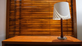 Wooden table with lamp with wooden shutters in background. In a hotel room Royalty Free Stock Images
