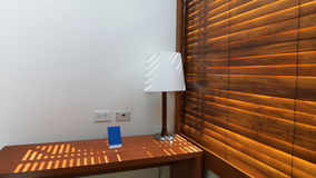 Wooden table with lamp with wooden shutters in a hotel room. Wooden table with lamp with wooden shutters with white wall background in a hotel room Stock Photography