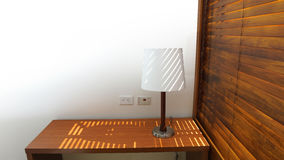 Wooden table with lamp with wooden shutters in a hotel room Royalty Free Stock Photo