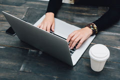 Wooden table with laptop and coffee. Freelance workspace Royalty Free Stock Images