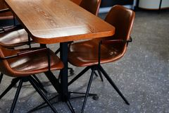 Wooden table and leather chairs or chairs, in a cafe, office or room. Stylish design, vintage style. Space for Breakfast, business stock photo