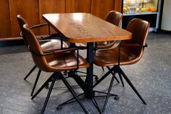 Wooden table and leather chairs or chairs, in a cafe, office or room. Stylish design, vintage style. Space for Breakfast, business. Meetings and corporate royalty free stock images