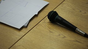On a wooden table lie a microphone and a diagram on a piece of paper. stock footage