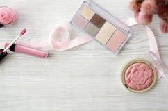 Wooden table with lipstick, nailpolish, blush and eyeshadows Royalty Free Stock Photo