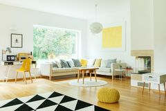 Wooden table in living room. Wooden table on white round carpet in living room with yellow pouf on floor and gold painting on wall Stock Images
