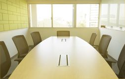 Wooden table in meeting room with sound absorbing wall sunlight through windows stock photography