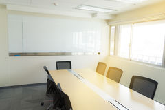 Wooden table in meeting room white board sunlight from window.  Royalty Free Stock Photos