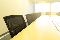 Wooden table in meeting room white board sunlight from window.  Stock Photos