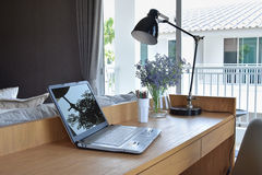 Wooden table in modern working area at home. Wooden table with computer notebook,pencil,lamp and artificial flowers in modern working area at home royalty free stock image