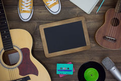 Wooden table of music composer. Guitar, ukulele, notebook, audio cassettes, microphone, tape recorder and blackboard with copy space. flat lay stock images