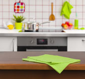 Wooden table with napkin on kitchen background Royalty Free Stock Photos