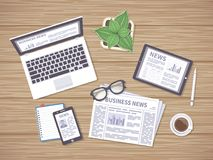 Wooden table with daily news on newspaper, tablet, laptop and phone. Many ways to get latest news. Stock Photos